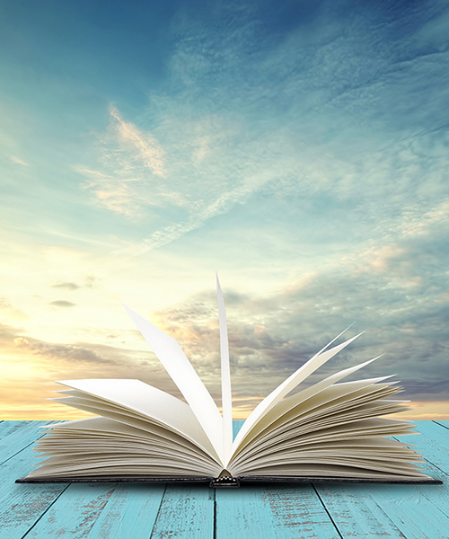 Open book on table with evening sky background